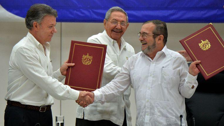 Blijde gezichten bij de Colombiaanse president Juan Manuel Santos (links), FARC-leider Timoleon Jimenez (rechts) en de Cubaanse president Raul Castro na de ondertekening van de wapenstilstand in juni. Beeld afp