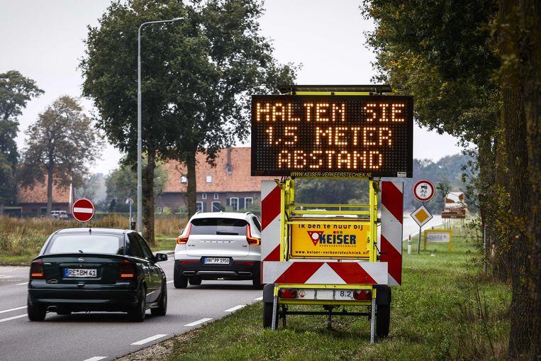 Een Informatiebord met oproep om 1,5 meter afstand te houden langs de weg N319 bij de Duitse grens.  Beeld ANP