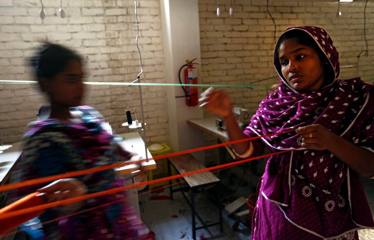 epa04173604 Survivors of the collapsed Rana Plaza garment factories building work in a factory called Oporajeo (The Undefeated), an initiative to rehabilitate the Rana Plaza Survivors, at Savar in Dhaka, Bangladesh, 20 April 2014. About 46 survivors work in the factory to run their families while the one-year anniversary of the collapse of the eight-story Rana Plaza building that left over 1,100 workers dead and about 2,500 rescued alive is coming up on 24 April 2013.  The Rana Plaza disaster highlighted unsafe conditions for many of the 4 million workers in the South Asian country's garment industry.  EPA/ABIR ABDULLAH Beeld EPA