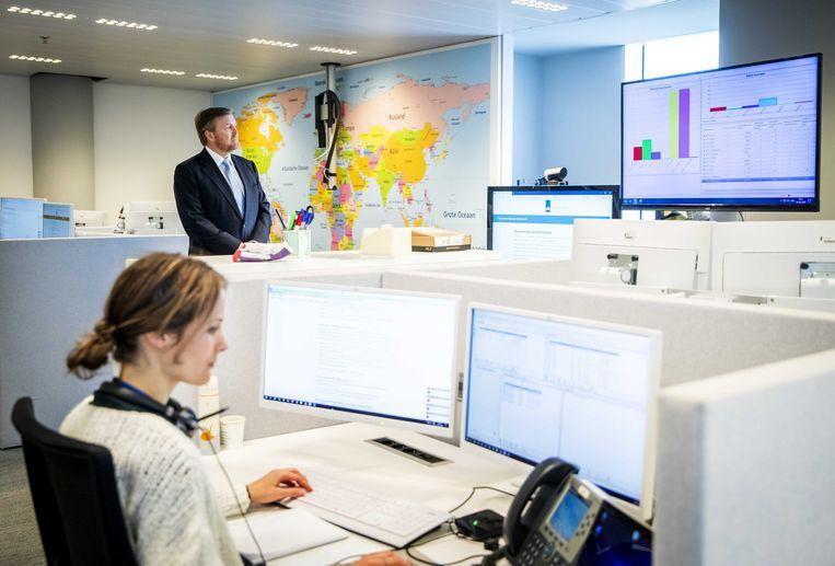 Koning Willem-Alexander tijdens een werkbezoek aan het 24/7 BZ contactcentrum van Buitenlandse Zaken in Den Haag, dat zich bezighoudt met de repatriëring van reizigers die zijn gestrand door het coronavirus. Beeld ANP