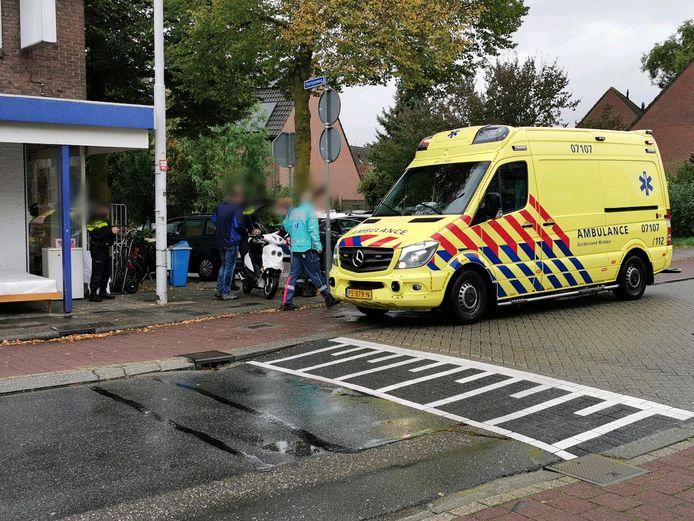 De scooterrijder krijgt eerste hulp na de aanrijding in Wageningen.