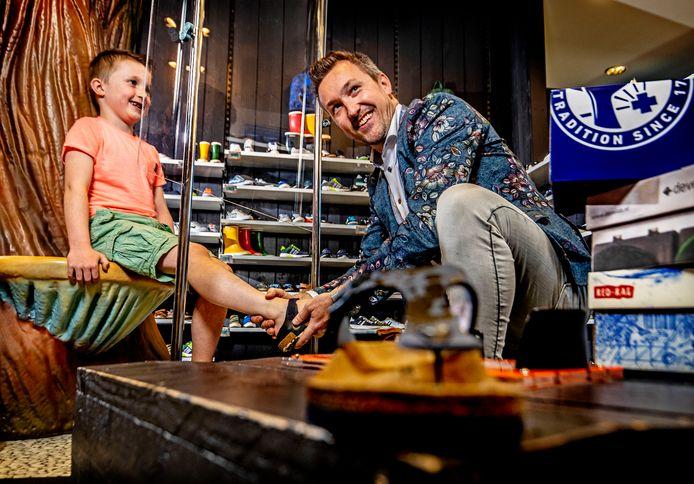 Jeffrey van Mourik past een paar schoenen vanachter corona-beschermend glas.