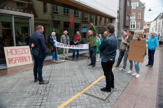 Wethouder Roy Geers (links) in gesrpek met tegenstanders van de bouwplannen in het Prins Hendrikpark.