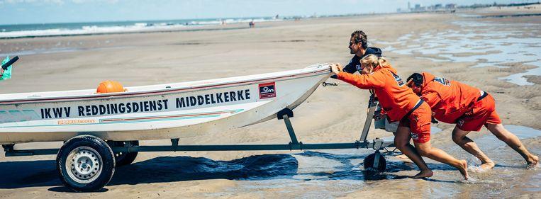 Redders Céline, Robby en Marc duwen de reddingsboot los uit het zand om hem dichter naar de waterlijn te brengen. Beeld Thomas Sweertvaegher