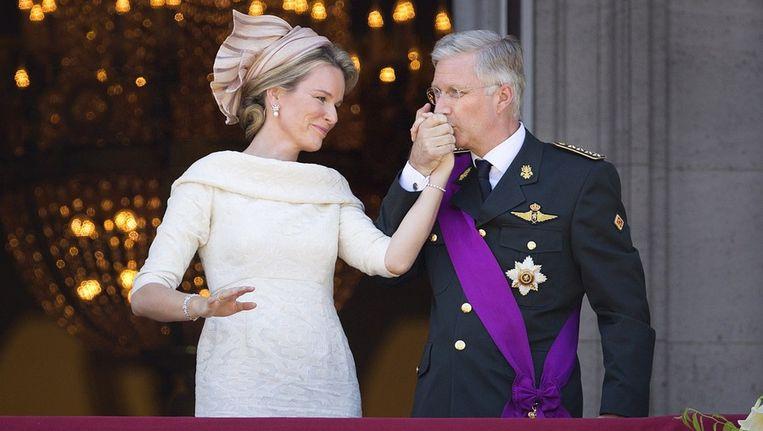 Koning Filip geeft zijn vrouw Mathilde een kus op de hand op het balkon van het Koninklijk Paleis in Brussel Beeld photo_news