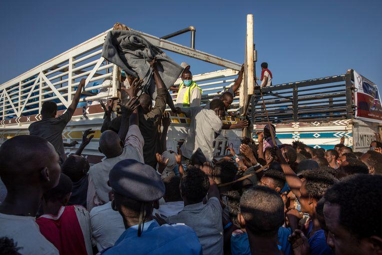 Vluchtelingen uit de Tigray regio ontvangen hulpgoederen in Soedan.  Beeld AP