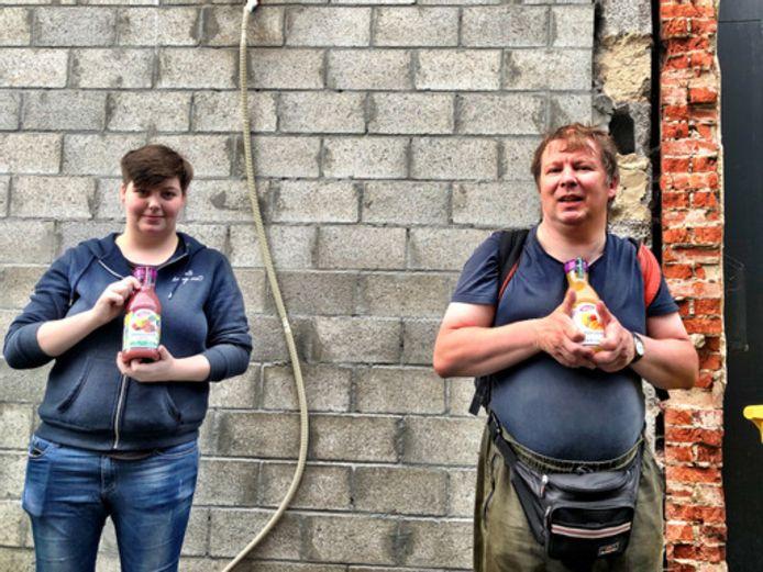 Medewerkers van vzw TWERK met een flesje Innocent sap voor de te renoveren muur van het bedrijf