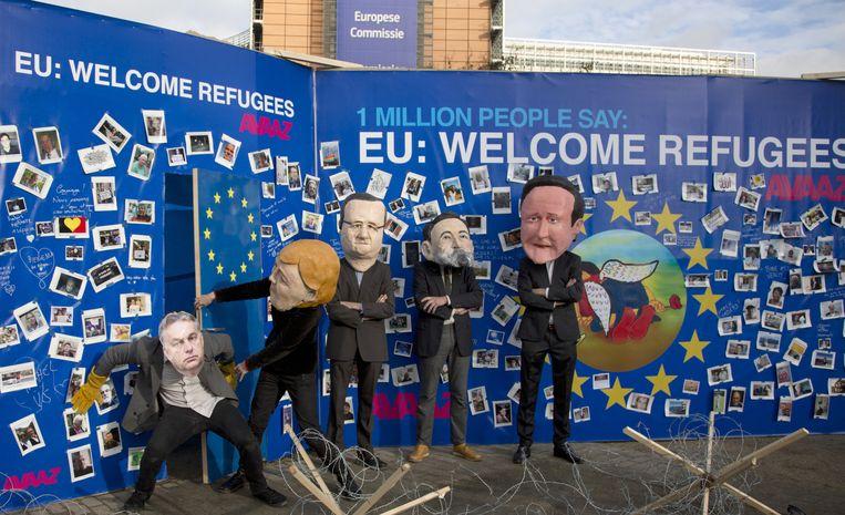 Activisten staan voor het EU-hoofdkwartier. Ze dragen karikaturen op hun hoofd van Europese leiders terwijl ze voor een muur staan waarop vluchtelingen welkom geheten worden. Beeld AP