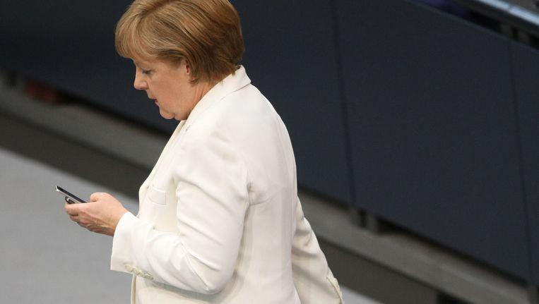 Bondskanselier Merkel met haar telefoon, eind juni vorig jaar. Beeld AFP