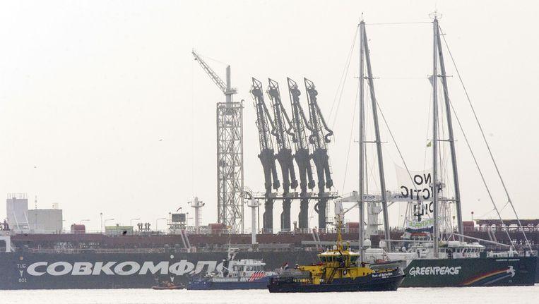 De Rainbow Warrior van Greenpeace ligt bij de Russische olietanker Michail Oeljanov (achtergrond), gevuld met de omstreden Noordpoololie, in de Maasvlakte Olie Terminal. Beeld anp