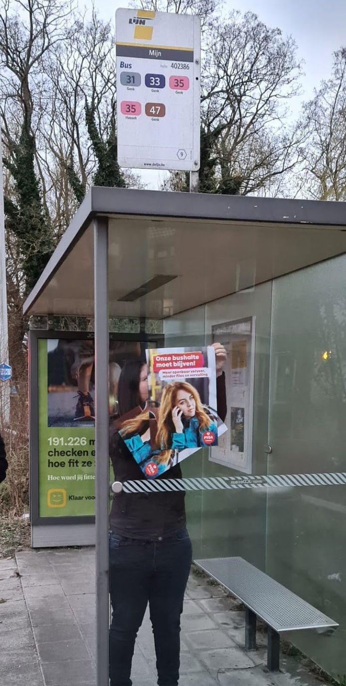 Voorzitter van PVDA Genk Michelle Heijens hangt een protestaffiche op aan een Genkse bushalte.