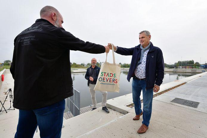 Sleuteloverhandiging van eerste ligplaats in de zwaaikom door wethouder Toine Theunis(r) en havenmeester Corné(m).