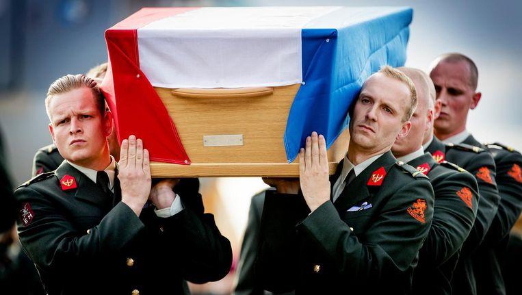 De lichamen van de omgekomen militairen komen aan op vliegbasis Eindhoven. Beeld anp
