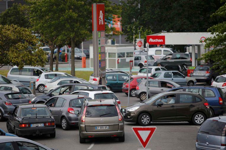 Aanschuiven aan het tankstation van een supermarkt in Saint-Sebastien-sur-Loire nabij Nantes Beeld REUTERS