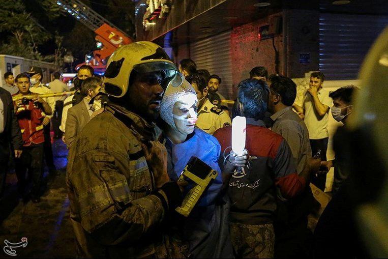 Een brandweerman helpt een gewonde vrouw na de explosie in een ziekenhuis in Teheran.  Beeld Reuters