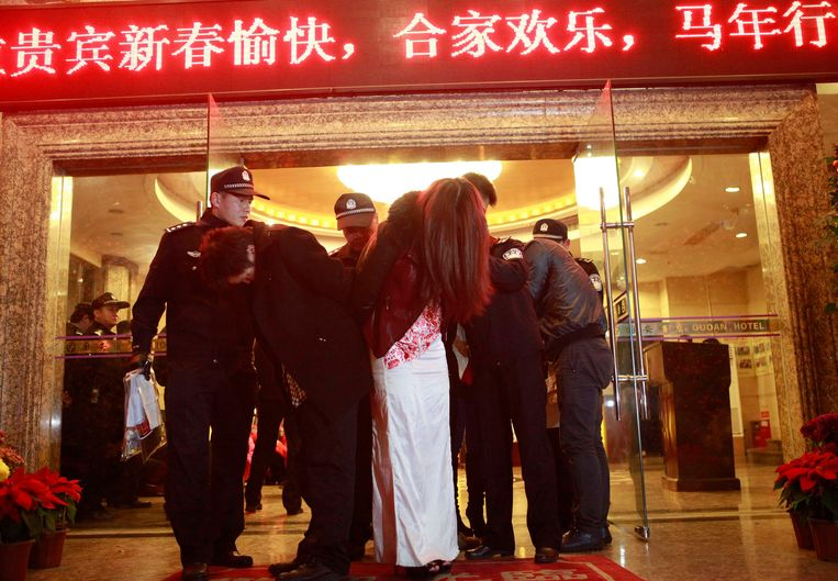 Een vrouw wordt weggeleid in de Chinese stad Dongguan na een actie van de politie tegen prostituees. Beeld REUTERS