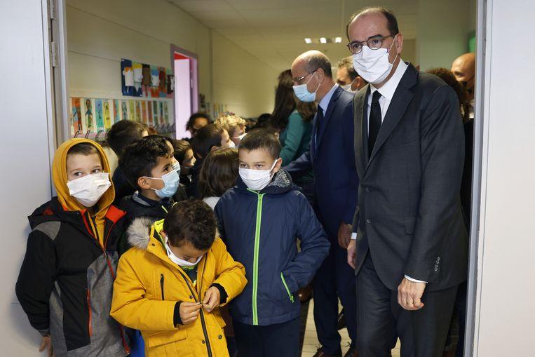 Premier Jean Castex (met wit mondmasker) en onderwijsminster Jean-Michel Blanquer (lichtblauw mondmasker) tijdens een bezoek aan een school in Conflans-Sainte-Honorine.  Beeld EPA