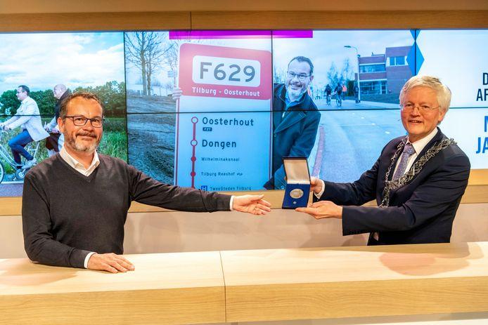Burgemeester Theo Weterings reikt de zilveren erepenning uit aan Mario Jacobs (l).