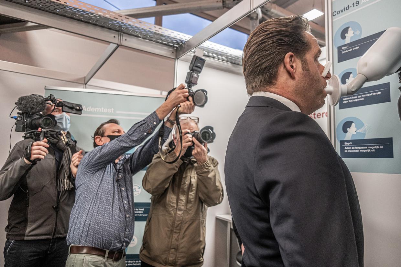 Minister Hugo de Jonge doet de SpiroNose-blaastest eind januari in een Amsterdamse teststraat. Beeld Joris van Gennip