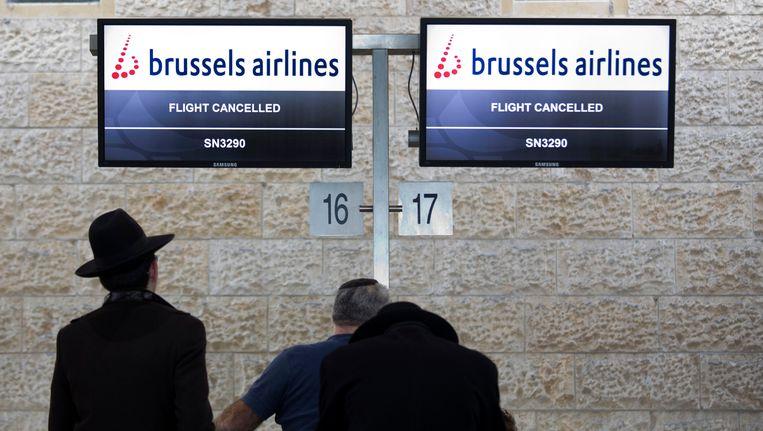 Passagiers in Tel Aviv wachten aan de balie van Brussels Airlines op nieuws over hun vlucht. Beeld AP