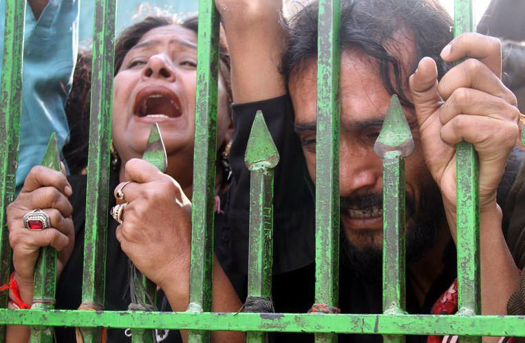 Honderden rouwenden verzamelden zich vanochtend bij het door een zware aanslag getroffen soefi-heiligdom in Sehwan, waar ook de eerste begrafenissen van de slachtoffers plaatsvonden. Veel gelovigen protesteerden tegen de Pakistaanse politie die het heiligdom onvoldoende beschermd zou hebben. Beeld EPA