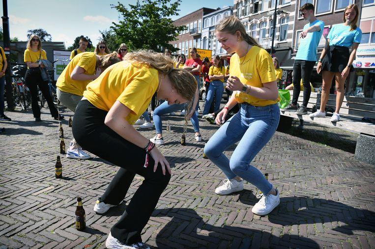 Studenten in Nijmegen doen een wedstrijd spijkerpoepen. Beeld Marcel van den Bergh / de Volkskrant