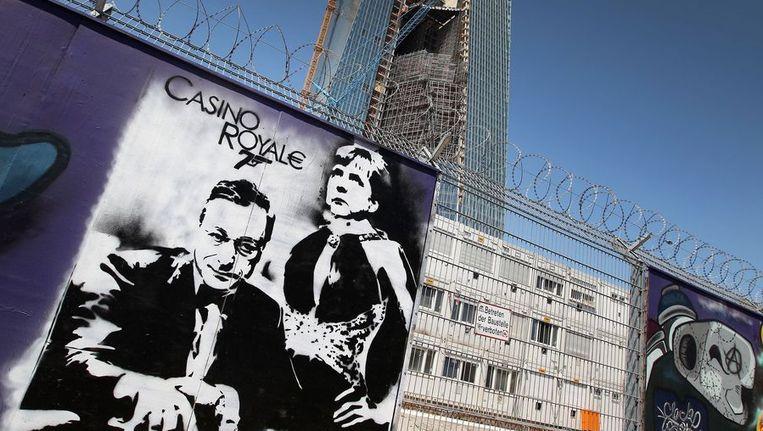 Een van de graffiti-werken toont Mario Draghi en Angela Merkel in een Casino Royale-setting. Beeld AFP