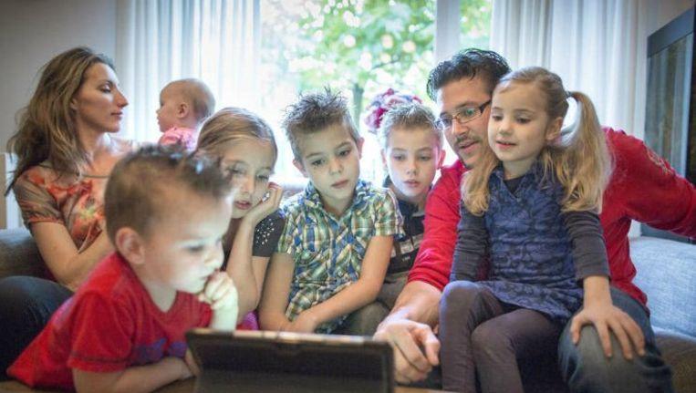 Vera en Arjan van Scharrenburg met de zes kinderen rond de iPad. De oudste twee antwoorden als eerste en vervolgens mogen de andere kinderen ook antwoorden. Beeld Herman Engbers