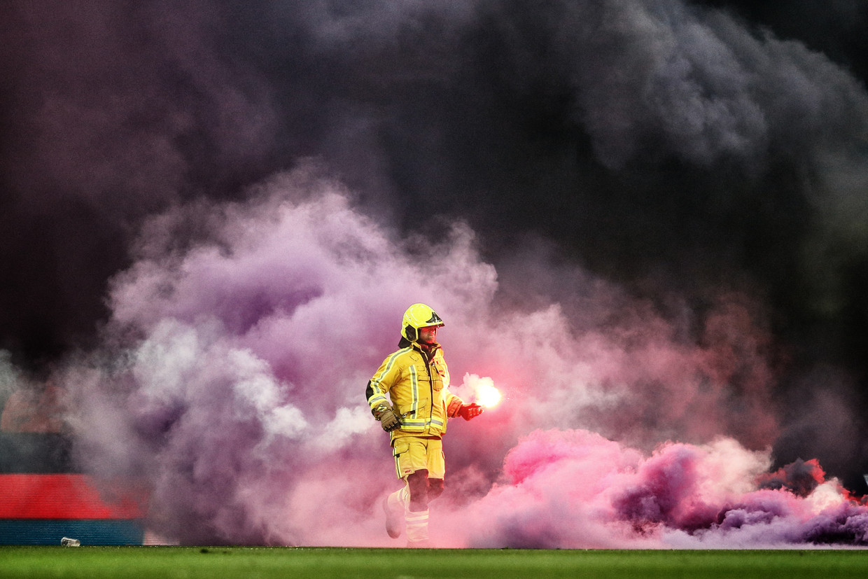De brandweer haalt vuurwerkpijlen weg van het veld tijdens de match vrijdag.