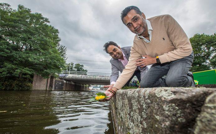 De Hindoestaanse pandit Vikash Tewarie en raadslid Kavish Partiman (L) laten bloemen te water. Eindelijk mag het in Den Haag.