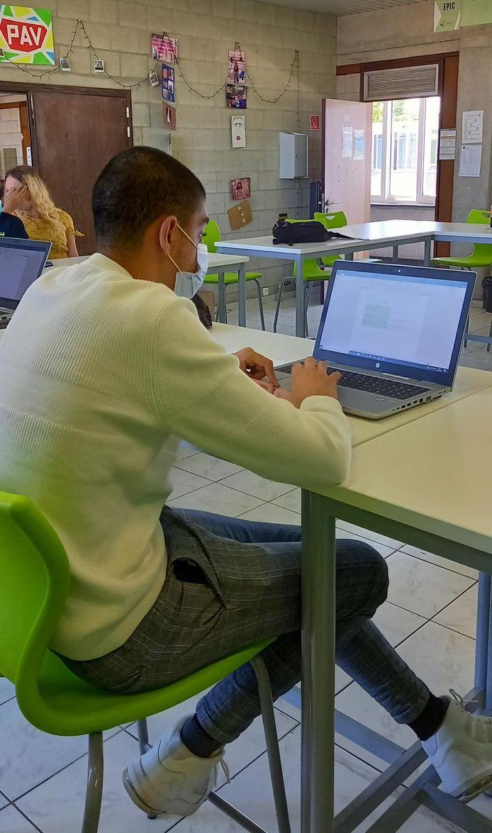 Een leerling van het Atheneum in Denderleeuw aan het werk achter de laptop.