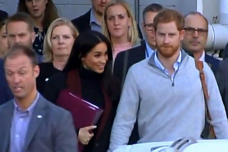 Harry en Meghan kwamen deze ochtend aan in Australië. Meghan hield daarbij twee roze mappen voor haar buik.