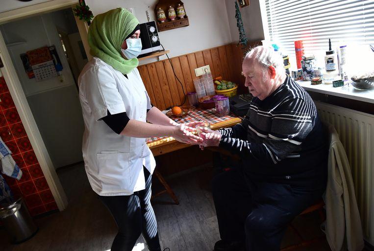Wijkverpleegkundige aan het werk in Renkum, voorjaar 2020. Beeld Marcel van den Bergh / de Volkskrant