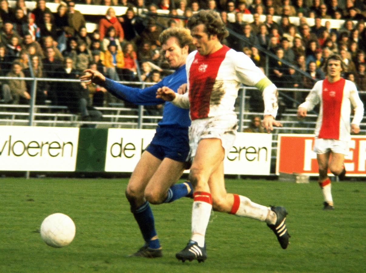 Piet Keizer in 1972 in duel met een speler van NAC. Rechts Johnny Rep.