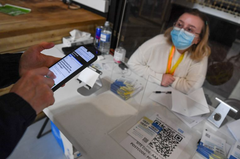 Een man geeft per mobiel zijn gegevens op voor een coronatest in Portsmouth.  Beeld Getty Images