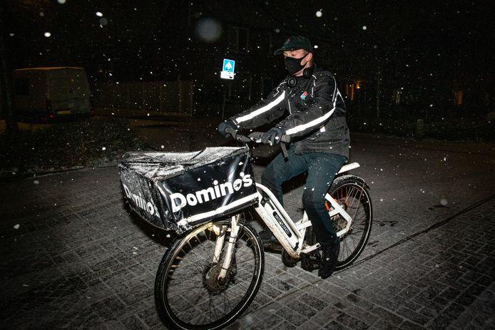 Pizzabezorger trotseert de elementen op weg naar een hongerige klant in Nijmegen.