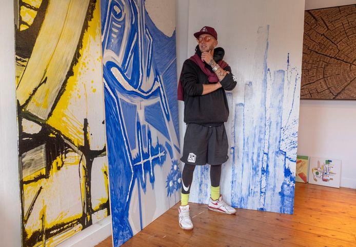 Michael Kluin voor een schilderij van paalhoofden.