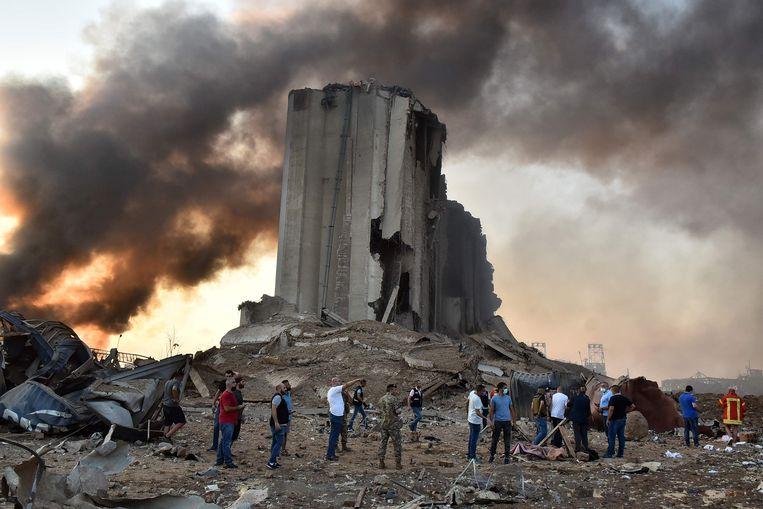 Mannen vergapen zich aan een van de vele ontplofte silo's in Beiroet. Beeld AFP