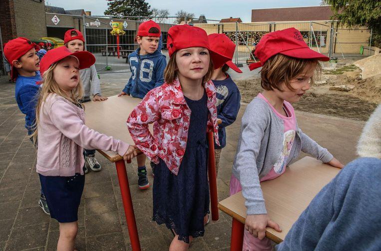 Kleuters brengen zelf tafels naar hun nieuwe klas.