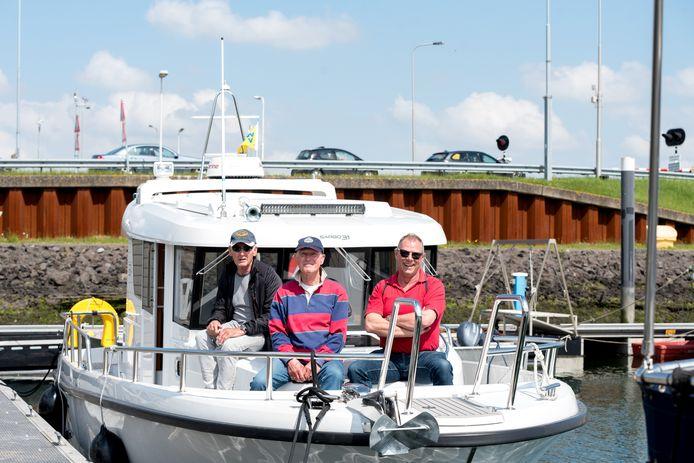 Schipper Frans van der Kruk, scheepsmaat Leen Borsje en Arno de Jonge uit Scharendijke op motorjacht Jack in de vissershaven van Bru. Op de achtergrond de auto's die over de bypass rijden, de enige weg die te gebruiken was het afgelopen half jaar.