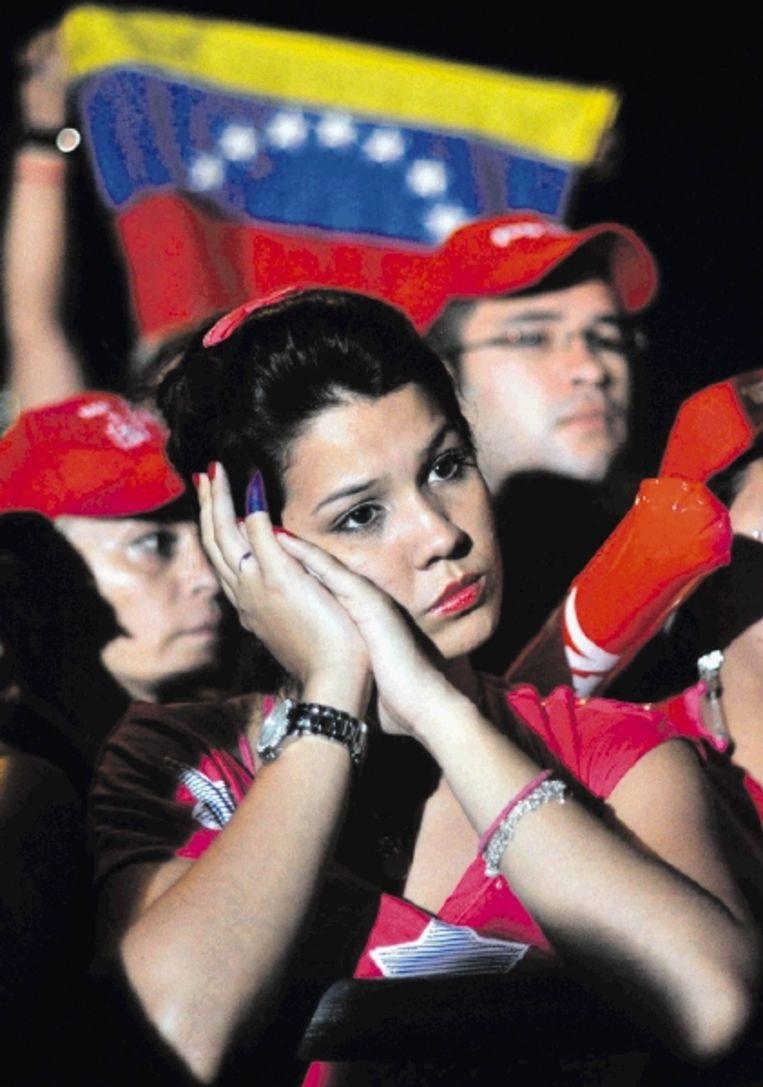 Een aanhangster van Hugo Chávez wacht bij het presidentiële paleis Miraflores gespannen op de uitslag. (FOTO AFP) Beeld AFP