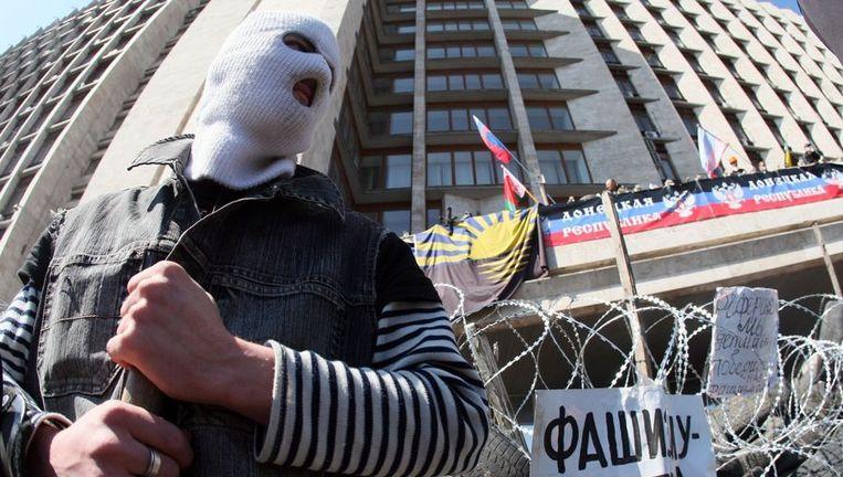 Een gemaskerde pro-Russische activist bewaakt een barricade in de stad Donetsk in het oosten van Oekraïne. Beeld AFP