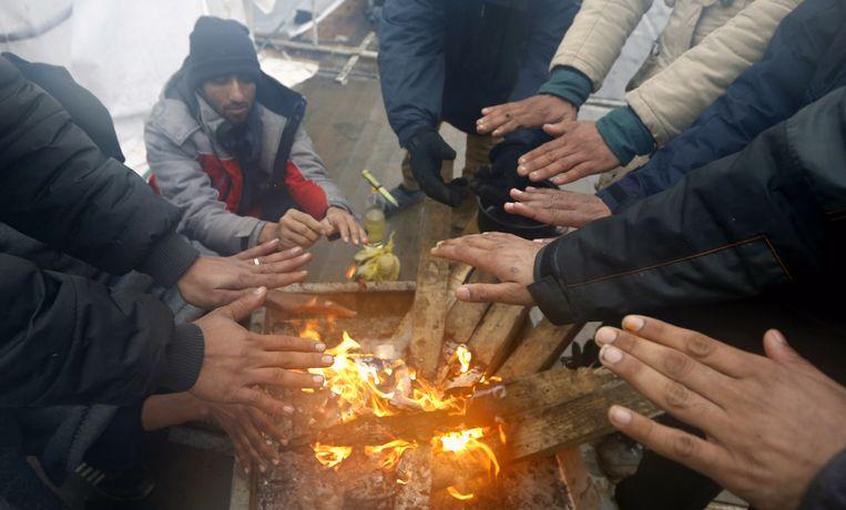 Vluchtelingen warmen zich op Nieuwjaarsdag op in het eerder afgebrande kamp Lipa in Bosnië. Beeld EPA