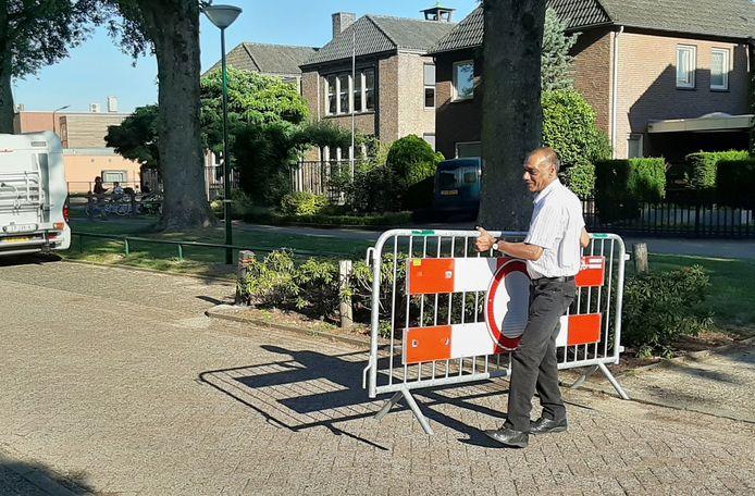 Een schoolmedewerker plaatst het dranghek midden op de straat Het Vijfeiken.