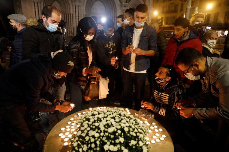Fransen steken kaarsen aan bij de kerk in Nice waar donderdag drie mensen werden neergestoken. Beeld EPA