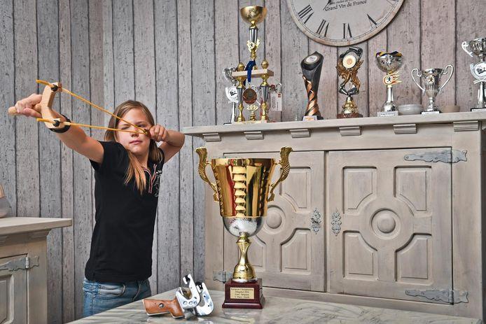 Taylor Pleysier mikt op doel met haar katapult. Naast haar staat de beker die ze afgelopen weekend op het Europese juniorenkampioenschap katapultschieten won.
