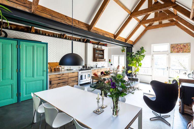 De keuken is een eigen ontwerp. Nigel en Thijs gebruikten upcycled hout van oude treinwagons.   Beeld Henny van Belcom