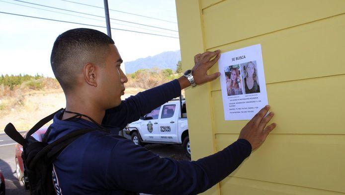 Een medewerker van de National System of Civil Protection van Panama bij een poster met de foto's van de vermiste vrouwen