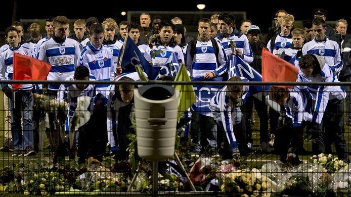 Leden van de club SC Buitenboys staan stil bij de bloemen die bij het hek langs het voetbalveld zijn neergelegd. De leden liepen mee in de stille tocht voor de overleden grensrechter Richard Nieuwenhuizen. Foto: ANP