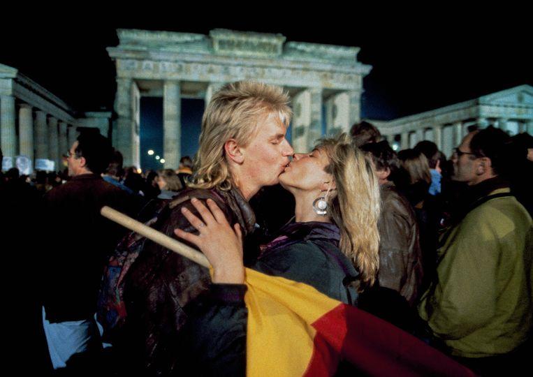 Een stelletje zoent voor de Brandenburger Gate om te vieren dat West-Duitsland en Oost-Duitsland weer bij elkaar hoorden. Beeld Hollandse Hoogte / Magnum Photos